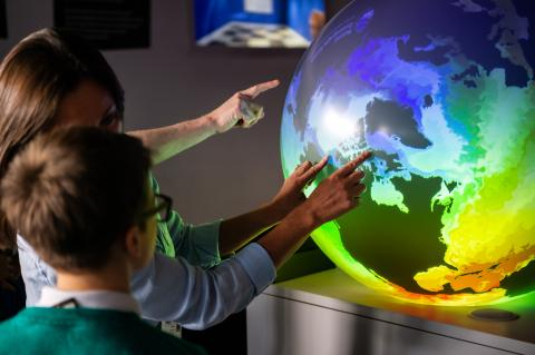 Delivering impact to the next generation at Winchester Science Centre Big Bang Event (February 2020). [cc] Scientists pointing and describing colourful models of the ocean, as they spin and move on a 3D globe, to a busy room of school children.