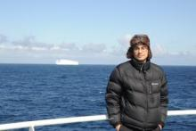 Alfred on the deck of RRS James Cook, iceberg in background