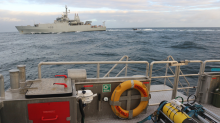 A submarine glider ready for deployment (front right) with HMS Enterprise in the background (Photo: NOC)