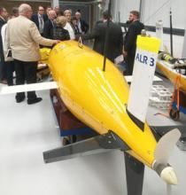 The group touring the Marine Robotics Innovation Centre, AutosubLR in foreground