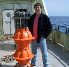 Professor Hughes onboard ship with an ocean bottom pressure recorder ready to launch