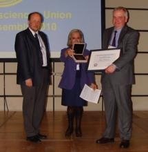Prof. Woodworth (right) accepting the award from Prof. Markku Poutanen (left) and Prof. Susanna Zerbini (centre) of the EGU